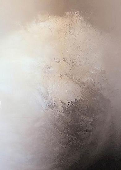 """Марсианская южная полярная шапка марсианской весной, состоящая из водяного льда и углекислого газа, запечатленная камерами аппарата Mars Global Surveyor (MGS) 12 сентября 2001 года, спустя четыре года после того, как он появился на орбите возле Красной планеты. Яркая область в центре изображения - это никогда не тающая часть южной полярной шапки поперечником около 420 км. Яркие области, которые окружают центр, представляют собой сезонные """"наносы"""", которые появились за время южной зимы, которая закончилась 17 июня 2001 года. Лето в южном полушарии начнется в середине ноября 2001 года. Фото с сайта Ames Research Center"""